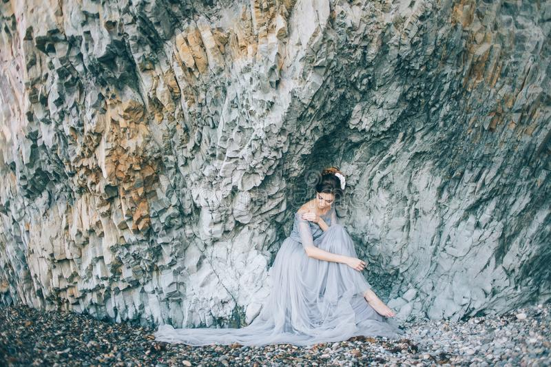 Attractive bride in a long dress sitting near the gray rock and straightens the dress. Wedding, lifestyle, happiness concept stock image