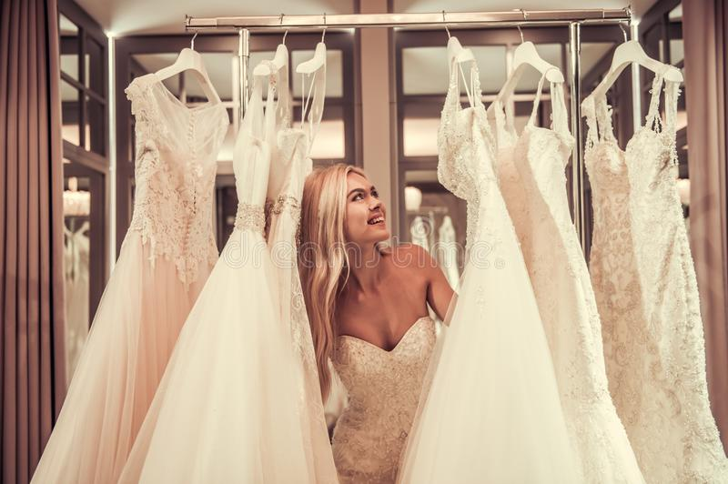 Attractive bride in wedding salon. Attractive young bride is smiling while choosing wedding dress in modern wedding salon stock photo