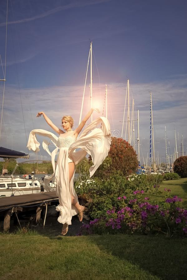 Attractive bride in yacht club. Attractive young bride in long beige dress in flight above green grass in yacht club near berth sunny day outdoor on natural blue royalty free stock photos