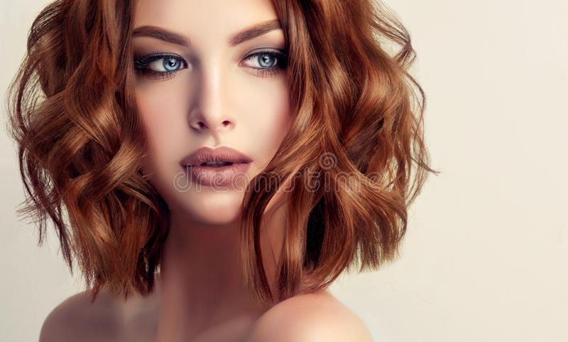 Attractive brown haired woman with modern, trendy and elegant hairstyle. Example of middle length,dense and curly hair.Gentle make up and long eyelashes royalty free stock image
