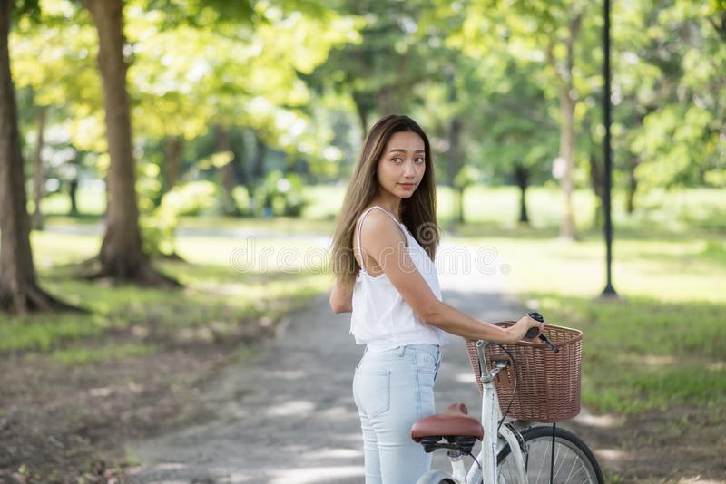 Attractive girl with bicycle in park stock photography