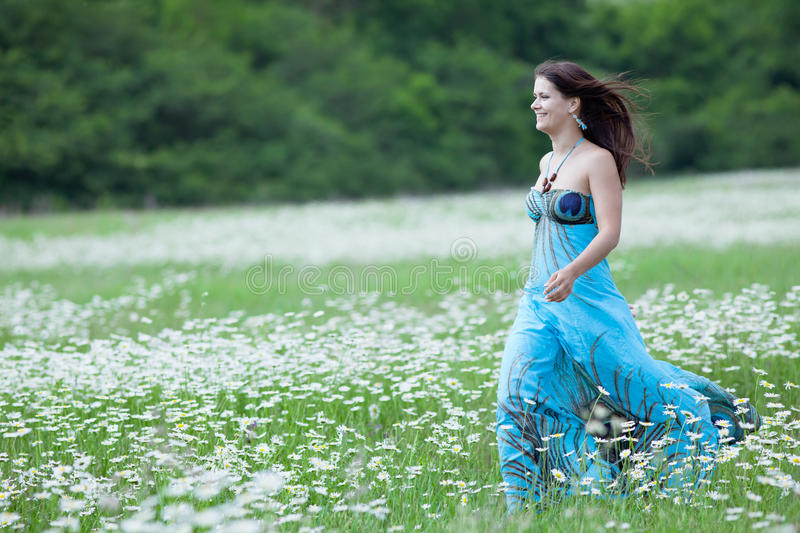 Attractive brunette in chamomile field royalty free stock photo