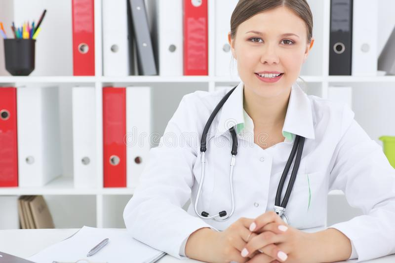 Attractive brunette doctor sitting at the desk in office background . stock image