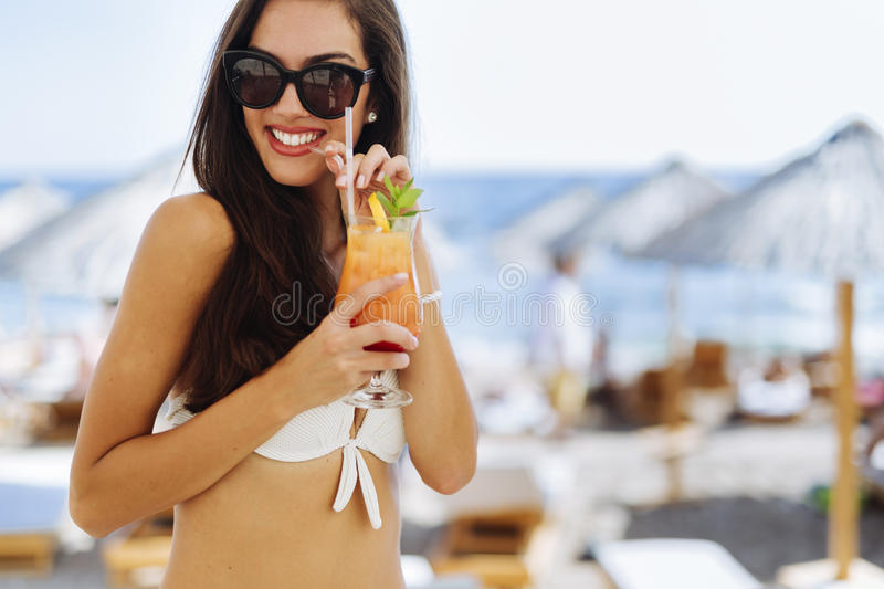 Attractive brunette drinking cocktails on beach royalty free stock images