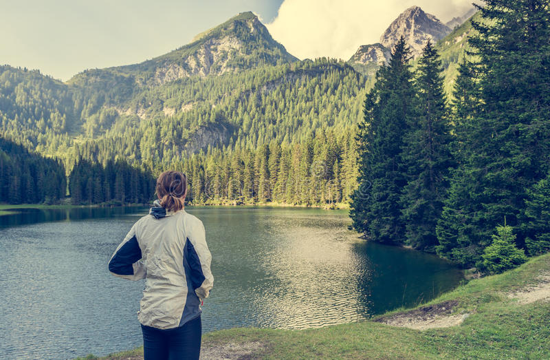 Attractive brunette enjoying lake view with surrounding forest. royalty free stock photography