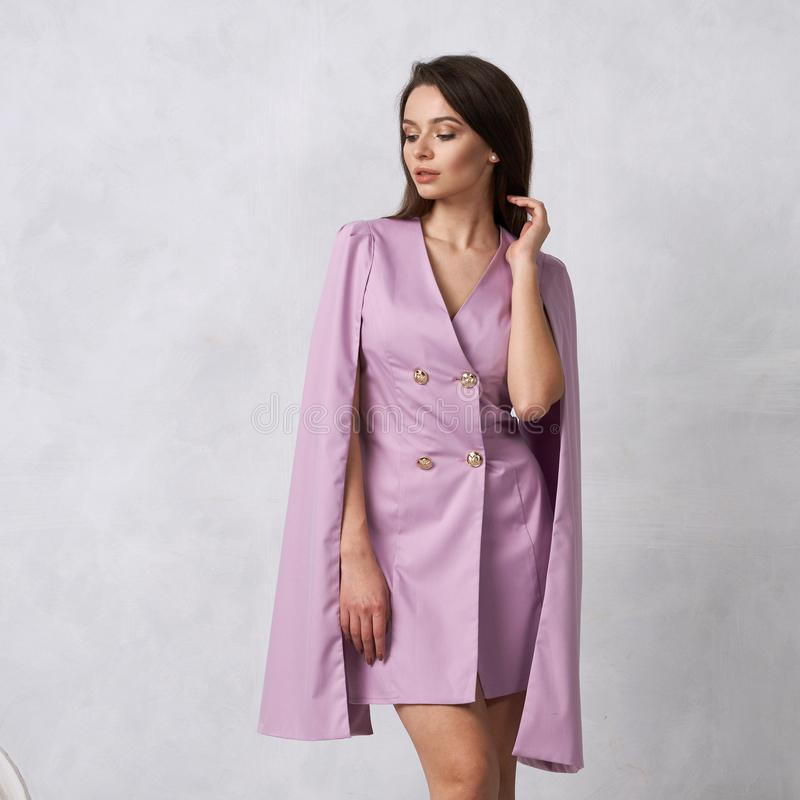Woman in mini purple dress with golden buttons and hanging sleeves royalty free stock images