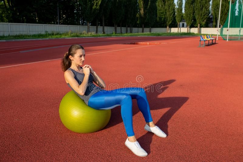 Attractive brunette girl doing exercises with fit ball at the st royalty free stock image
