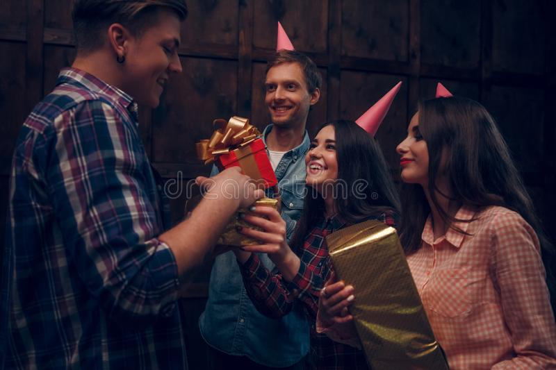 Amazing friends celebrate birthday and give presents to their friend. royalty free stock photo