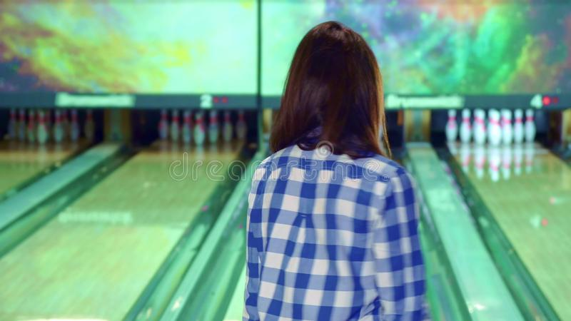 Girl knocks down pins at the bowling. Attractive brunette girl knocking down pins at the bowling. Pretty young woman releasing the ball. Caucasian female bowler royalty free stock photos