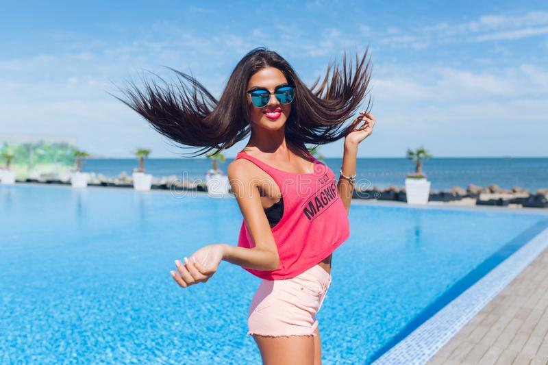 Attractive brunette girl with long hair is jumping to the camera near pool. She wears pink T-shirt with shorts and royalty free stock photography