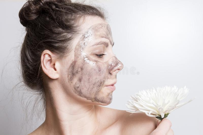 Attractive brunette girl with white flower in facial mask. Cleaning and protection of skin of face. Skin care. Portrait of girl with black cosmetic mask stock photos