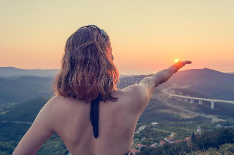 Attractive brunette holding a sun in her hand. royalty free stock photo