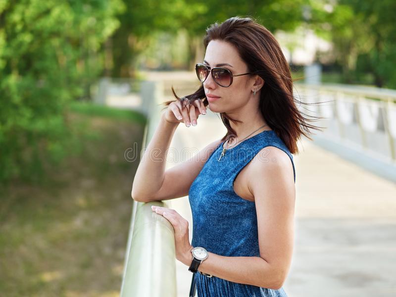 Attractive brunette woman in sunglasses and blue jeans dress has emotional phone conversation on mobile phone on park bridge outdo royalty free stock photos