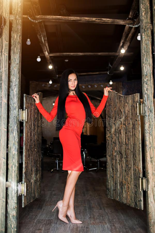Attractive brunette with long hair and a slender figure standing in kasern dress. Beautiful model posing on a dark interior. And he looks at the camera with a stock photo