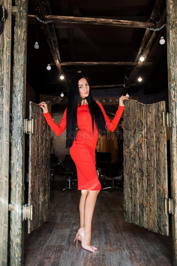 Attractive brunette with long hair and a slender figure standing in kasern dress. Beautiful model posing on a dark interior and he stock photos