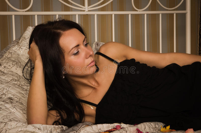 Attractive brunette lying on the bed royalty free stock image