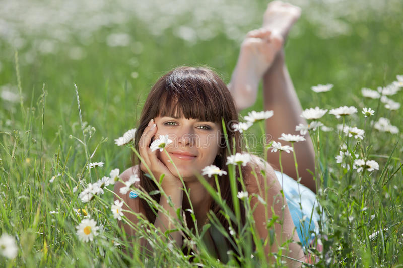 Attractive brunette lying in chamomile field royalty free stock photos