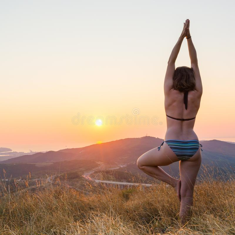 Attractive brunette performing yoga form at sunset. royalty free stock images