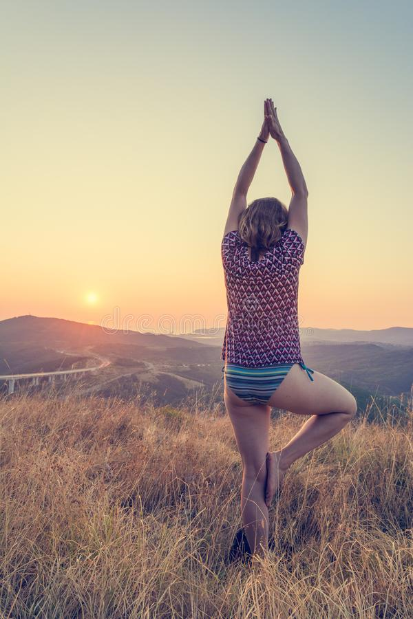Attractive brunette performing yoga form at sunset. royalty free stock photo