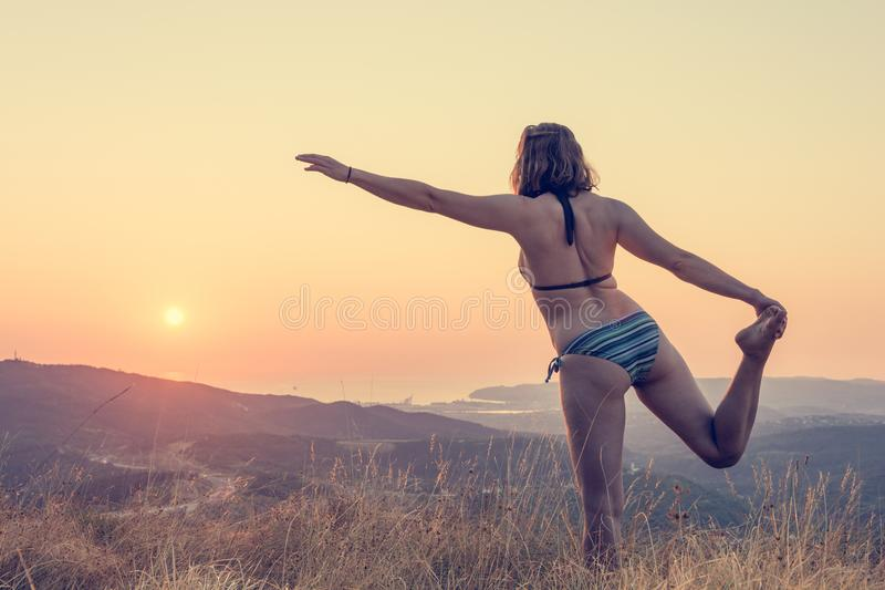 Attractive brunette performing yoga form at sunset. stock photos