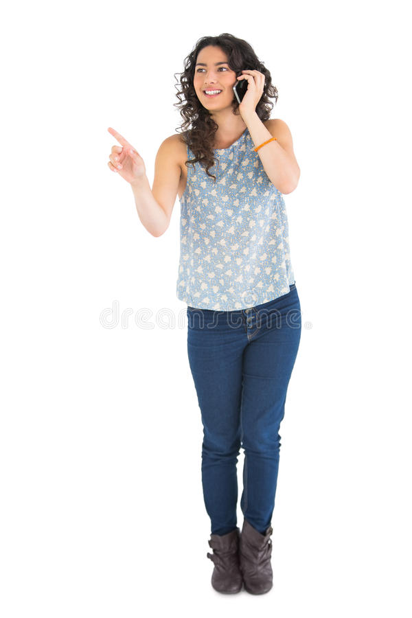 Download Attractive Brunette Pointing At Something While Having Phone Call Stock Photo - Image: 33188766