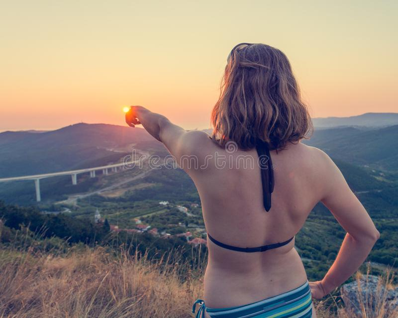 Attractive brunette pointing towards setting sun. royalty free stock images