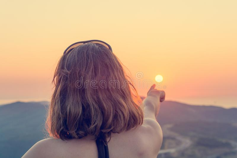 Attractive brunette pointing towards setting sun. stock photography