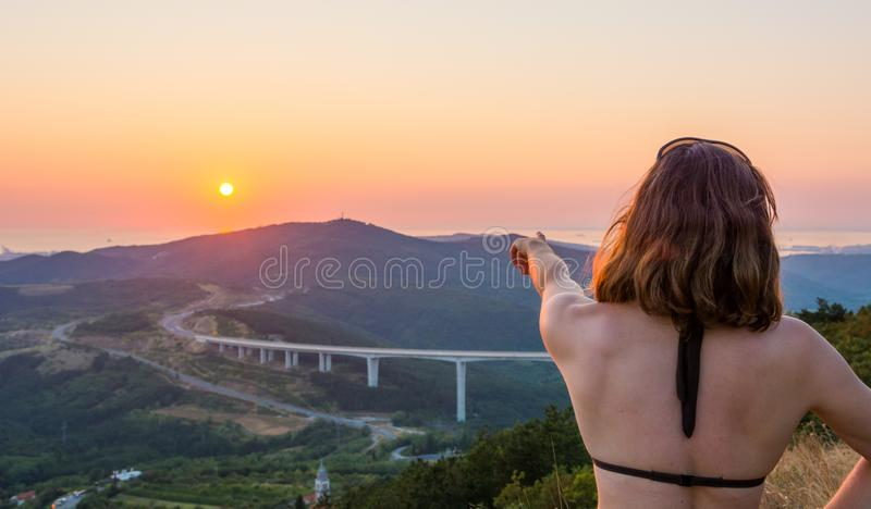 Attractive brunette pointing towards setting sun. stock image