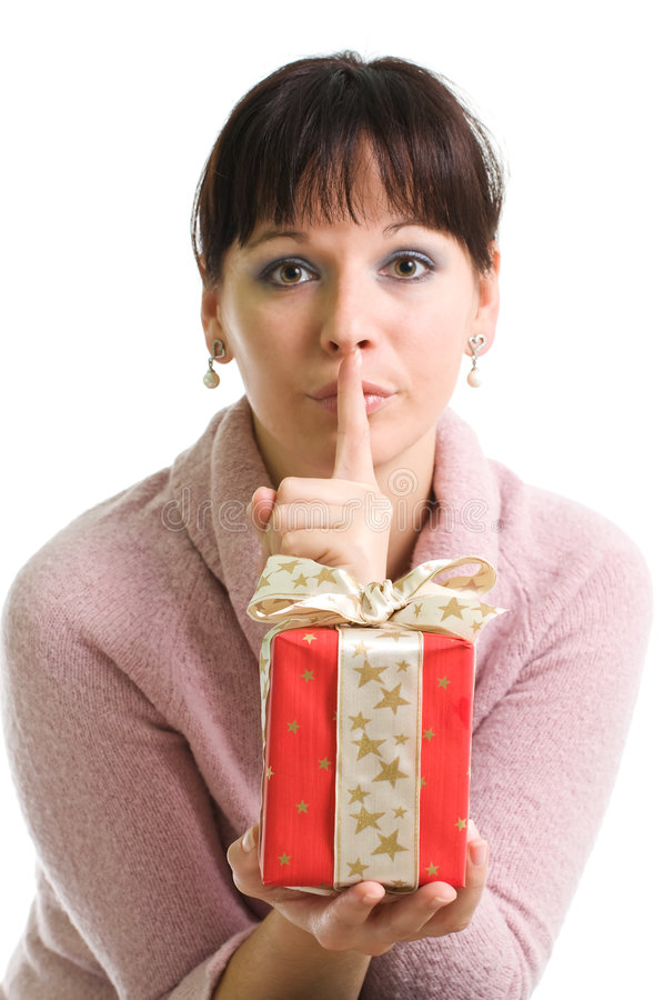 Attractive brunette shows secret Christmas present. Young brunette and her secret Christmas present isolated over white stock photography