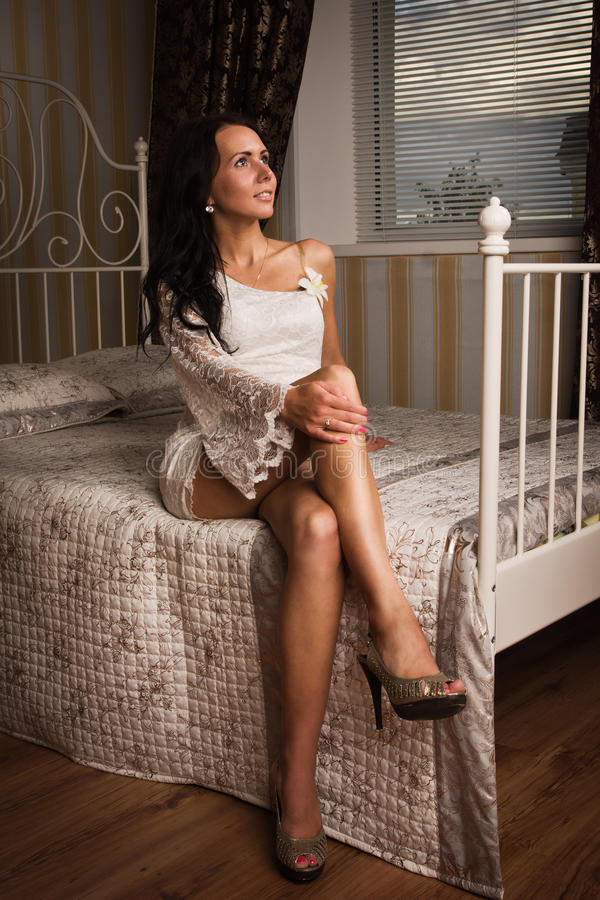 Attractive brunette sitting on the bed stock images