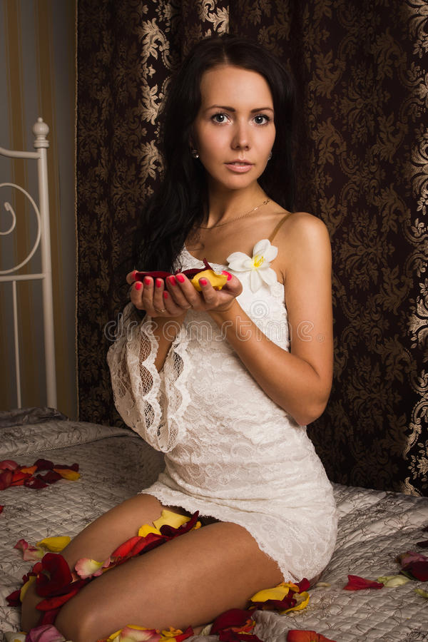 Attractive brunette sitting on the bed royalty free stock photos