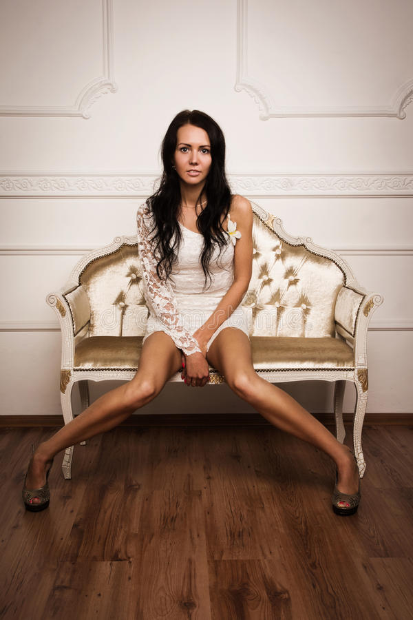 Attractive brunette sitting on the couch stock image