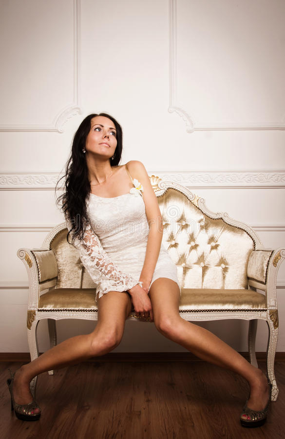 Attractive brunette sitting on the couch royalty free stock photography