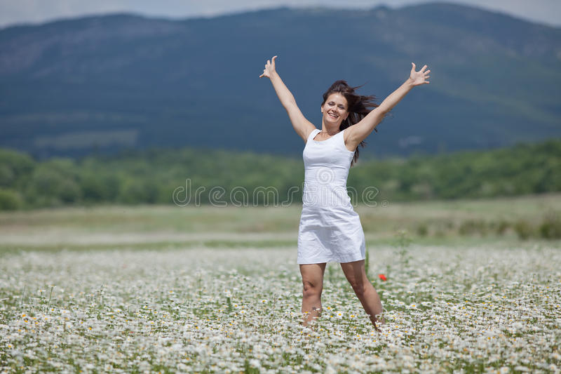 Attractive brunette walking along chamomile meadow royalty free stock image