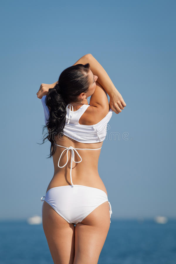 Attractive brunette in white swimwear undressing on the beach stock photography