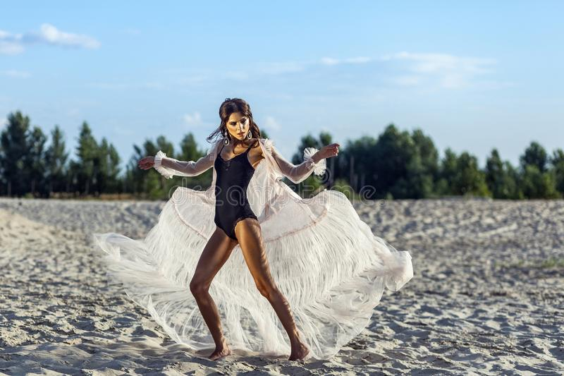 Attractive brunette woman in black body and translucent beach cover up posing on sandy beach at sunset. fluttering dress with. Hands and looking away. Fashion stock image