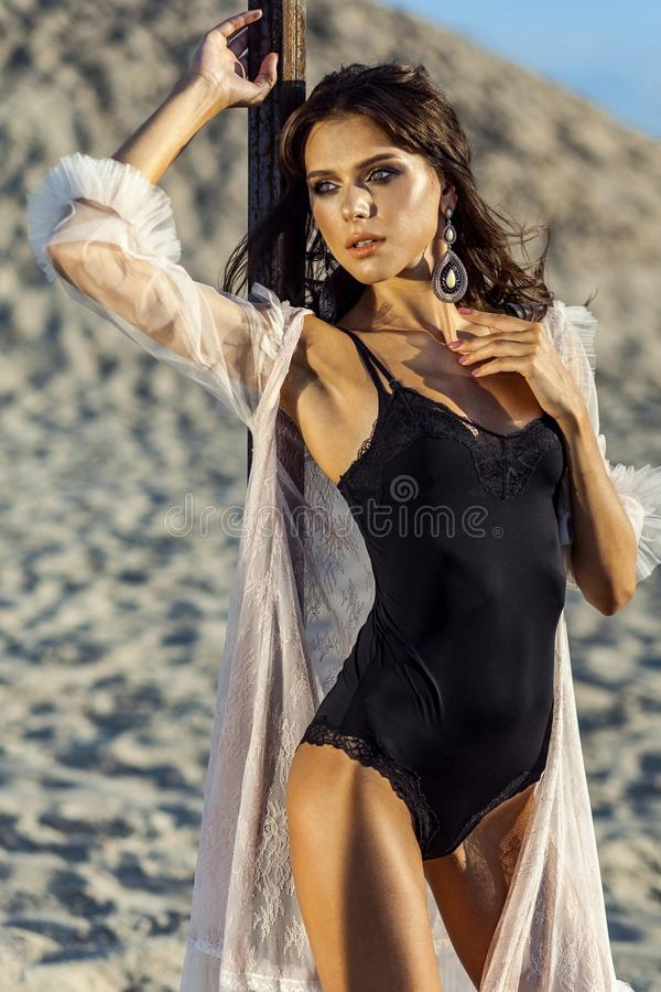 Attractive brunette woman in black body and translucent beach cover up posing on sandy beach at sunset. standing and looking away. Fashion outdoor shot in the stock photo