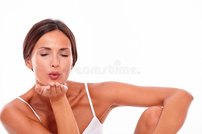 Attractive brunette woman blowing a kiss royalty free stock photo
