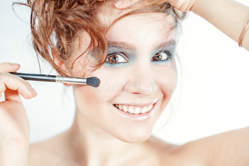 Attractive brunette woman doing make up royalty free stock photography