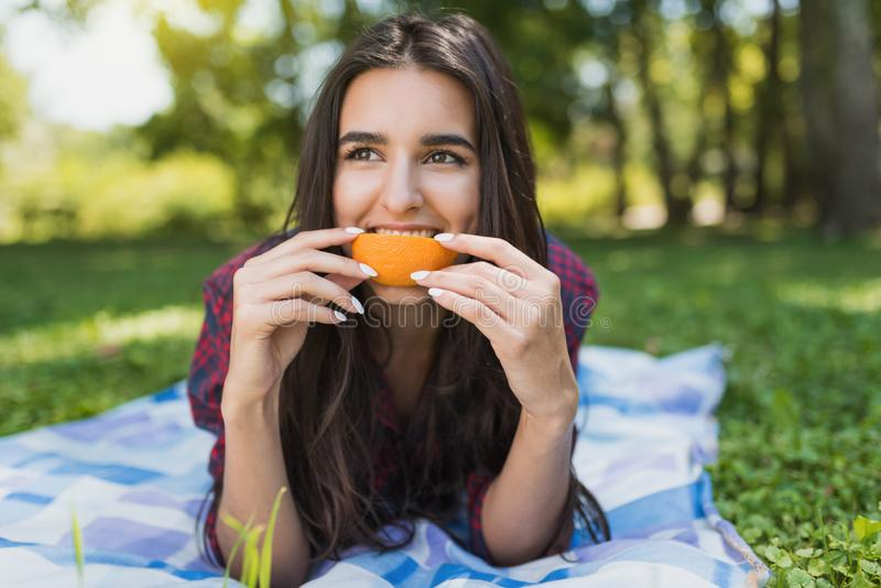 Attractive brunette woman lying on green grass in outdoor eating orange fruit, copy space for your advertising message or content royalty free stock image