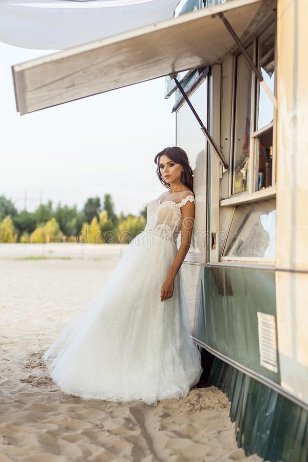 Attractive brunette woman with makeup and hairstyle wearing white wedding dress while posing and lean near street food car. stock image