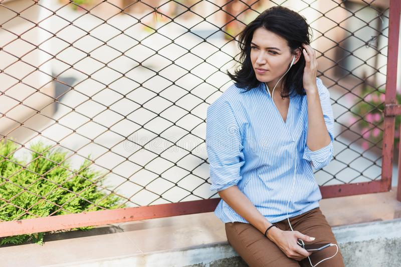 Attractive brunette woman with mobile phone looking away and waiting friend on the city street. Young brunette pensive business stock photo