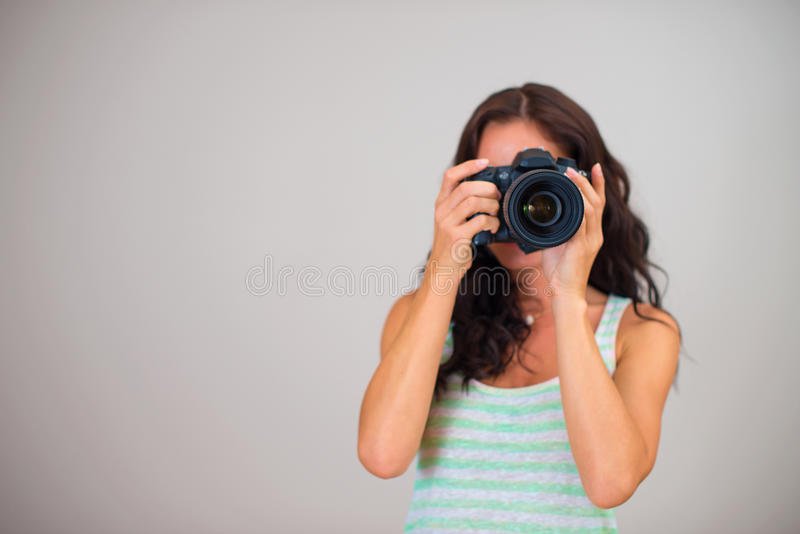 Attractive brunette woman-photographer. Attractive brunette woman-photographer takes pictures. Space for your text royalty free stock images
