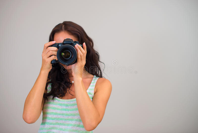 Attractive brunette woman-photographer. Attractive brunette woman-photographer takes pictures. Space for your text stock photos