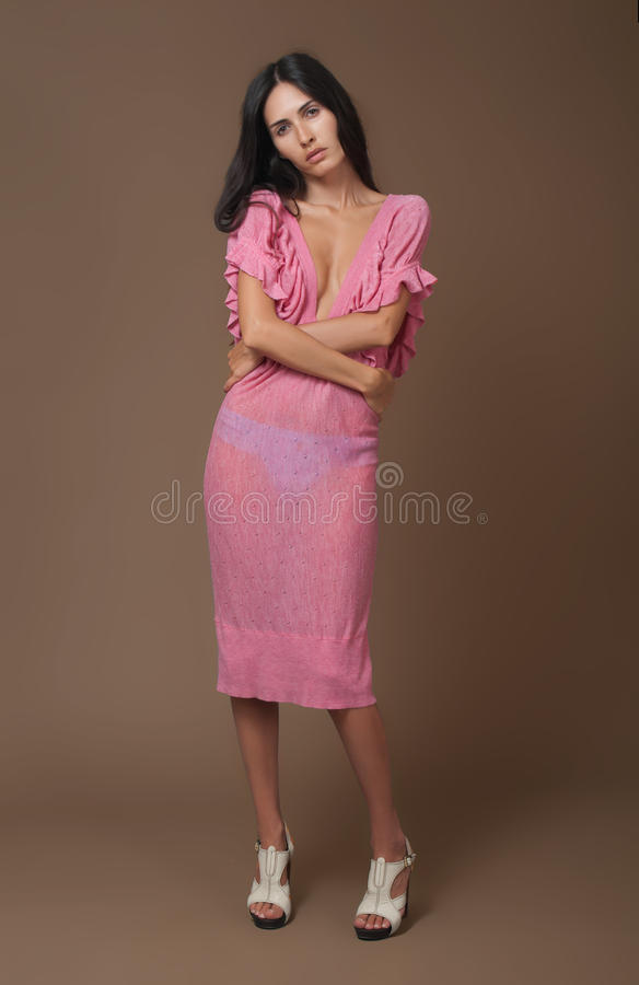 Attractive brunette woman in pink dress royalty free stock photography