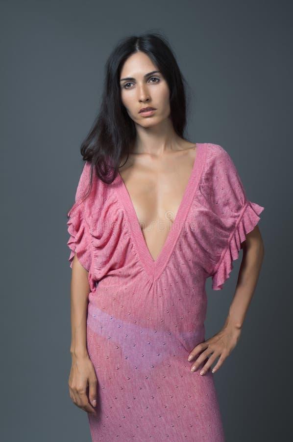 Attractive brunette woman in pink dress