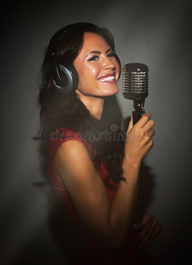 Attractive brunette woman recording a song. Attractive brunette woman recording a song in music studio stock photos