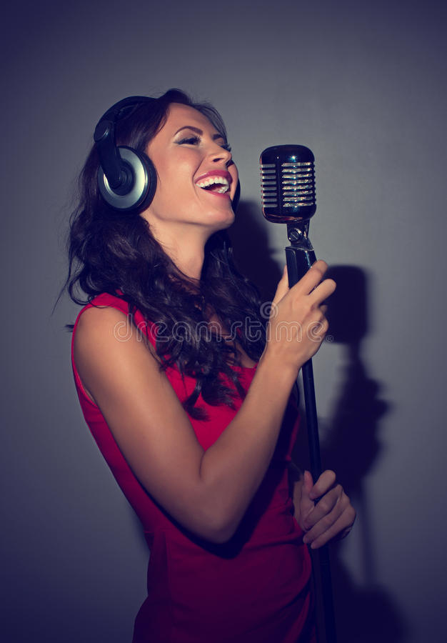 Attractive brunette woman recording a song. Attractive brunette woman recording a song in music studio royalty free stock photo