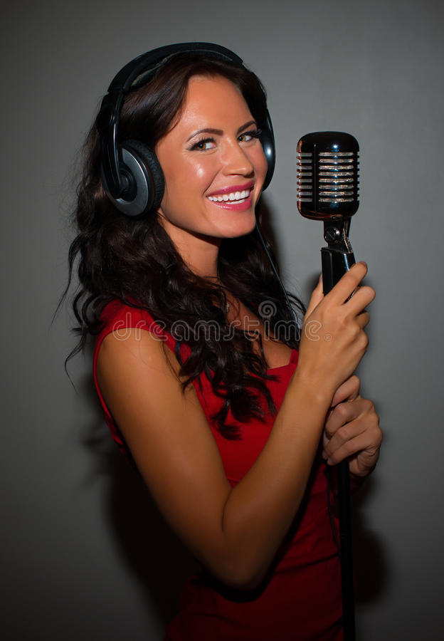 Attractive brunette woman recording a song. Attractive brunette woman recording a song in music studio royalty free stock images