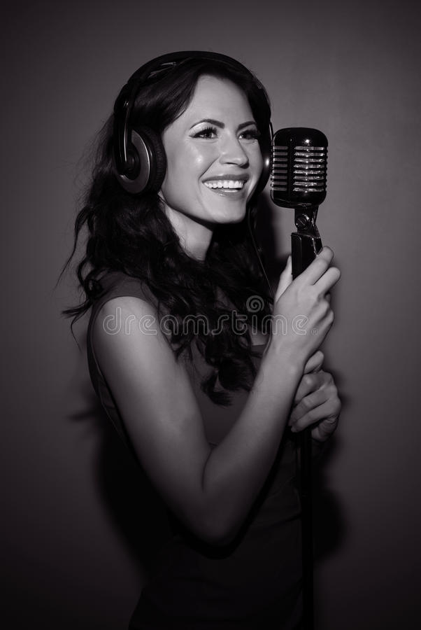 Attractive brunette woman recording a song. Attractive brunette woman recording a song in music studio. Black and white photo stock photo